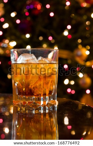 Christmas Liquor Cocktail in a Crystal Glass on a Reflective Table with Christmas Lights Out of Focus in the Background - stock photo