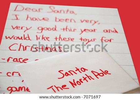 Christmas list written by a child with an envelope addressed to santa at the north pole -on red background