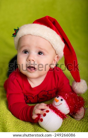Christmas little baby boy with Santa hat and snowman - stock photo