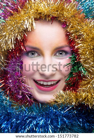 Christmas masquerade portrait of young woman with tinsel - stock photo