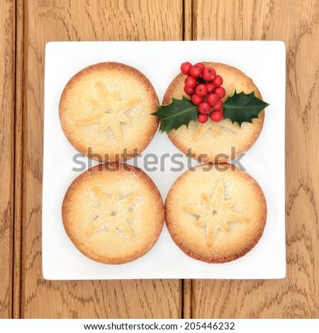 Christmas mince pie cakes and holly on a plate over oak background. - stock photo