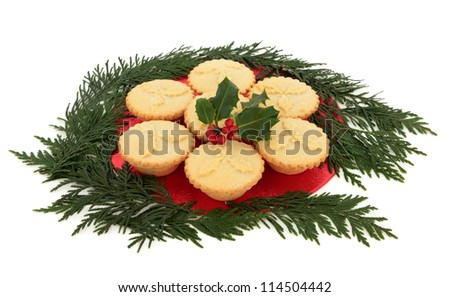 Christmas mince pie group with holly and red berry leaf sprig surrounded by cedar leaf sprigs over white background.