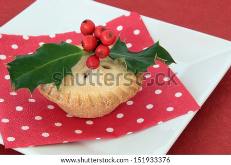 Christmas mince pie on a white porcelain plate with holly and polka dot serviette over red background. - stock photo