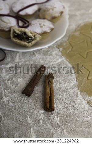 Christmas mince pies on the white plate with cinnamon sticks - stock photo