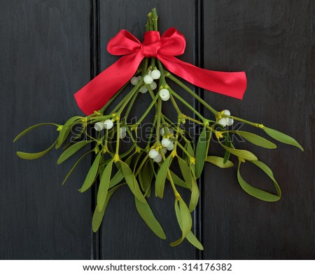 Christmas mistletoe with red ribbon bow over dark wood background. - stock photo