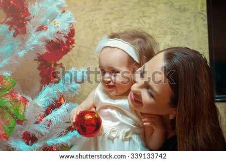 Christmas mood. Mother decorates the Christmas tree with his little daughter for the first time. New year. - stock photo