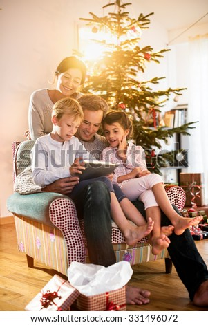 Christmas morning, cheerful family sitting in the living room having fun with the digital tablet that Santa Claus brought her, behind the decorated christmas tree, the sunshine give a cozy atmosphere - stock photo