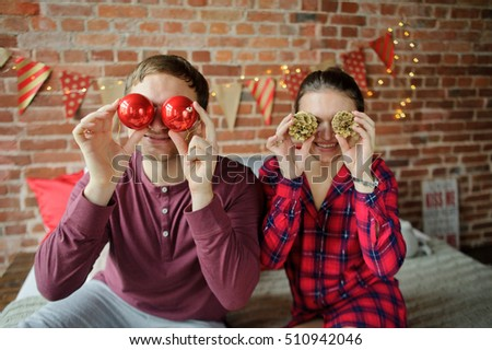 Christmas morning. Young couple sitting on the bed. Man and woman are in a good mood. They fool around. Christmas Holidays is the perfect time to relax and chat. Merry Christmas and a Happy New Year.
