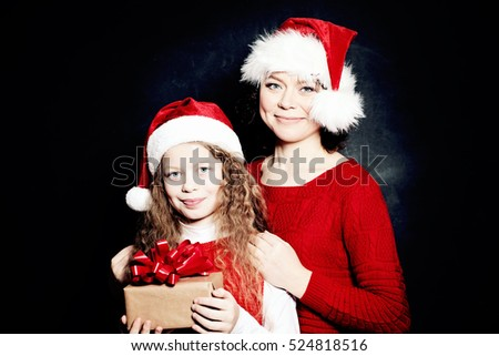 Christmas Mother and Daughter in Santa Hat Having Fun with Gift. Happy Family in Red Winter Jumper