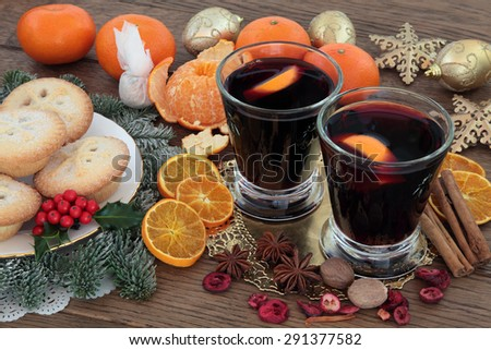 Christmas mulled wine, mince pies, spices, fruit, baubles and winter greenery over oak background. - stock photo