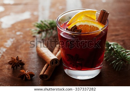 Christmas mulled wine or gluhwein with spices and orange slices on rustic table, traditional drink on winter holiday, magic light, selective focus - stock photo