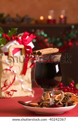 Christmas mulled wine with gift bag with presents in background - stock photo