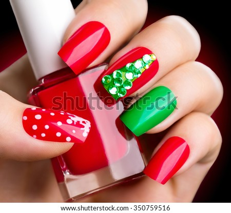 Christmas Nail art manicure. Winter Holiday style bright Manicure with gems Christmas tree and snowflakes. Bottle of Nail Polish. Beauty hands. Trendy Stylish Colorful Nails, Nailpolish - stock photo