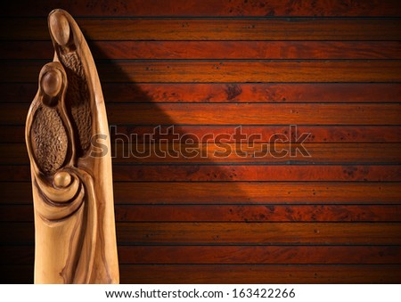 Christmas Nativity Scene on Wood Wall / Wooden Christmas Crib with Mary, Joseph and baby Jesus on wooden background with shadows - stock photo