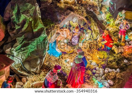 Christmas Nativity scene, the Blessed Virgin Mary and Saint Joseph watch over Holy Child Jesus in a manger,  the ox and the donkey are warming while the three wise men bring gold, frankincense, myrrh - stock photo