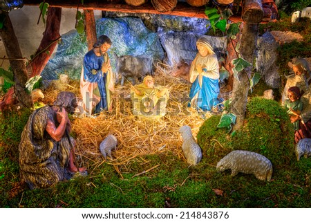 Christmas nativity scene with baby Jesus, Mary & Joseph in barn with flock of sheeps and shepherds - stock photo