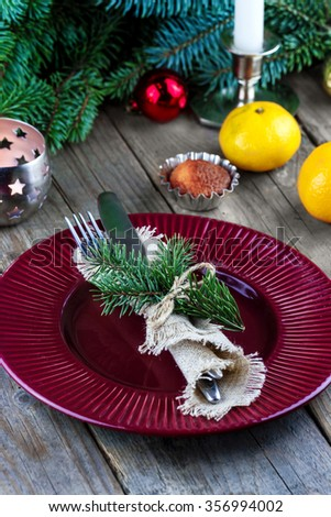 Christmas (New Year) table appointments. Fork and knife decorated thuja branches and twine bow with wine glass on wooden background - stock photo