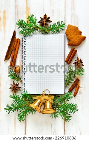 Christmas notebook background on light wooden surface decorated xmas tree branches, cookies, bells and spices - stock photo