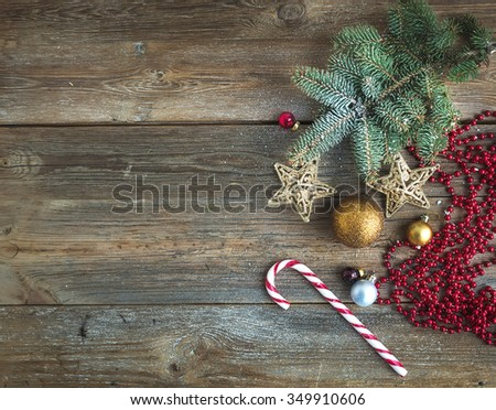 Christmas or New Year rustic wooden background with toy decorations, candy cane and fur tree branch, top view, copy space