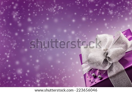 Christmas or Valentine's purple gift with silver ribbon abstract purple background - stock photo