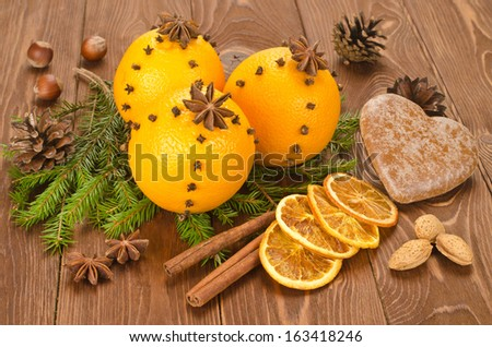 Christmas orange decorated with cloves on a wooden table - stock photo