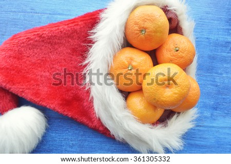 Christmas orange.Santa hat filled with Christmas gifts