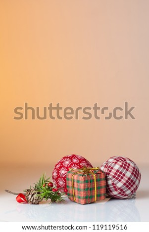 Christmas ornament: Christmas gifts in colorful wrapping with golden ribbons and christmas balls with an orange background