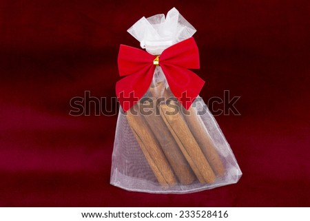 Christmas ornament - cinnamon sticks in bag with red bow on red velvet background - stock photo