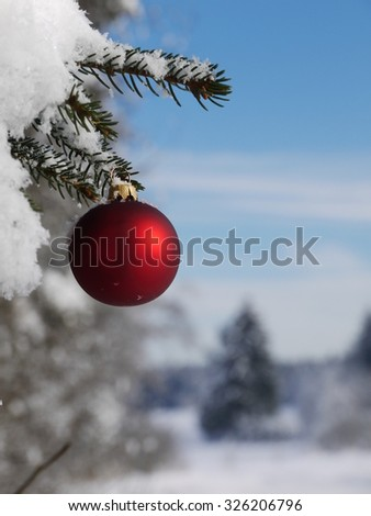 Christmas ornament hanging on a pine tree outside in the snow - stock photo