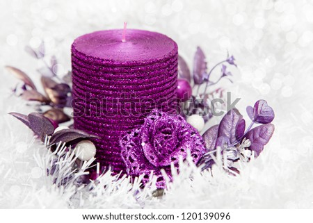 Christmas Ornament with candle on white snowy background