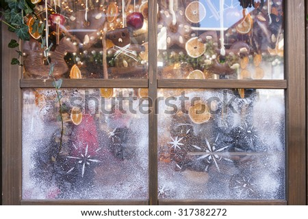 Christmas ornaments behind window - stock photo