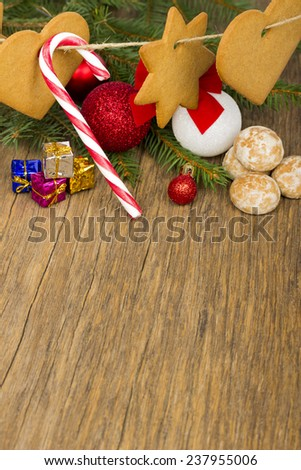 Christmas ornaments - gingerbread and Christmas candy cane, balls, gifts and fir on old wooden background - stock photo
