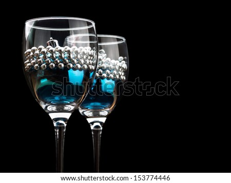 Christmas ornaments in wine glasses - stock photo