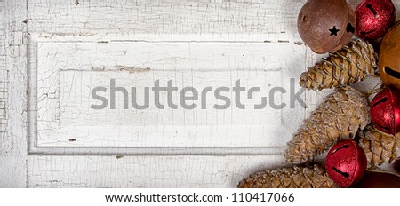 Christmas ornaments pine cones and rusty bells on antique cracked wood panel - stock photo