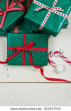 Christmas packages with green paper and diferent red bows on a white wooden table