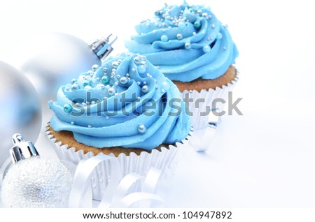 Christmas party cupcakes in blue icing, silver ornaments and ribbons - stock photo