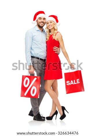 christmas, people, sale, discount and holidays concept - happy couple in santa hats hugging with red shopping bags - stock photo