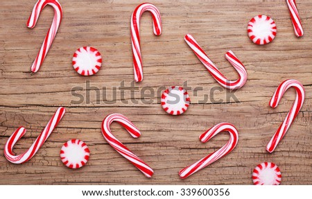 Christmas. Peppermint Candy and Canes on old wooden background