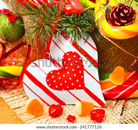 Christmas pine twigs, heart, christmas balls with pine cones, sweets and jellies on sacking background - stock photo
