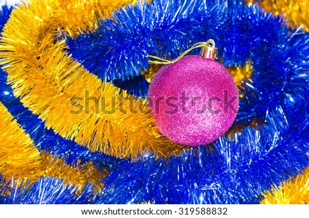 Christmas pink toy lies on christmas decorations. tinsel - stock photo