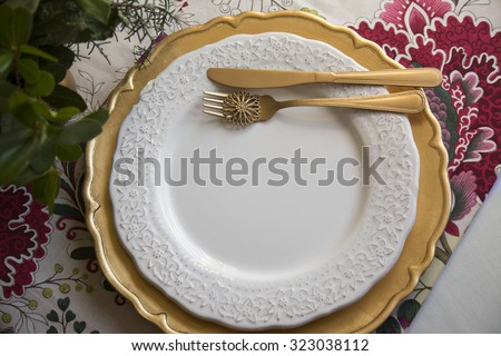 christmas place setting, table ready for lunch, on golden plates and white patterned background in flowers - stock photo