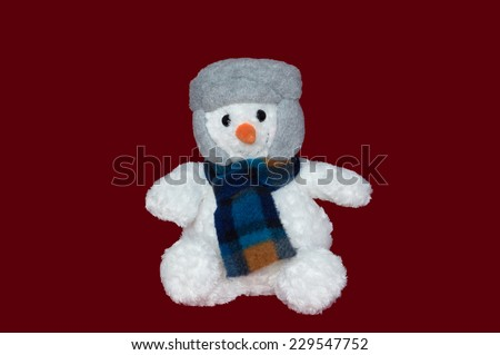 Christmas - Plush Snowman with Hat and Scarf on red background - stock photo