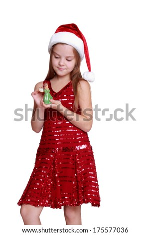 Christmas Portrait of a beautiful little child girl wearing a santa hat holding decorative doll/little girl wearing red dress with santa hat on Holiday theme
