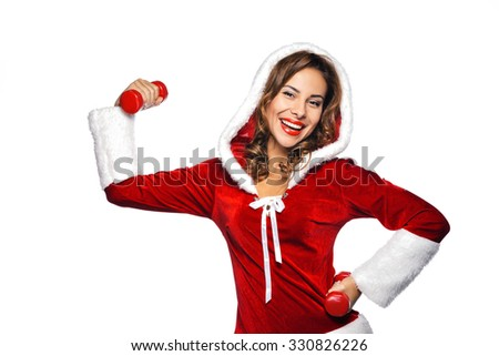 Christmas portrait of beautiful mixed-race santa girl. Young sexy brunette woman wearing santa claus clothes. Snow Maiden holding red dumbbell on white background - stock photo