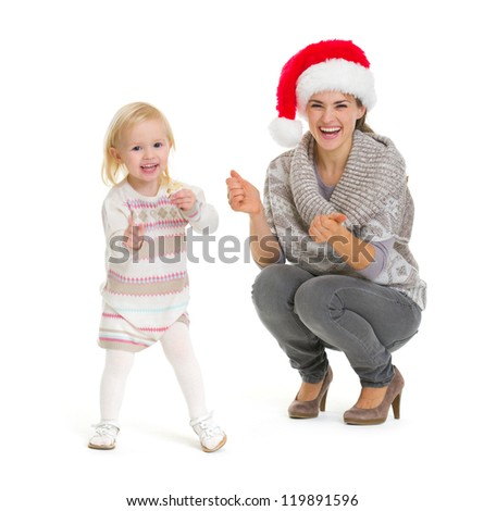 Christmas portrait of happy mother and baby girl dancing - stock photo