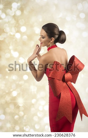 christmas portrait of sexy brunette pin-up girl turned on her back with elegant hair-style, red dress and golden jewellery  - stock photo