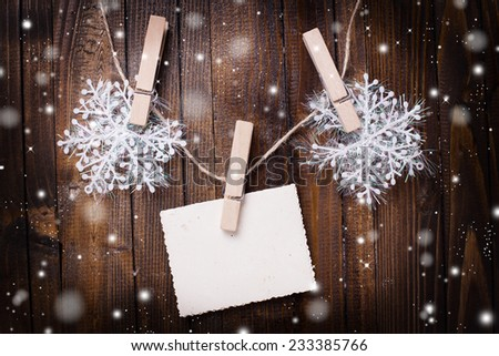 Christmas postcard. Empty paper and snowflakes on wooden background. Christmas decorations. - stock photo