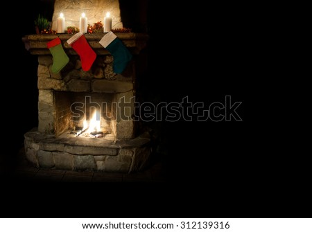 Christmas postcard template. colorful stocking on fireplace background. green, red, dark blue socks with gifts. Chimney place with candles.  Copy space, black background.