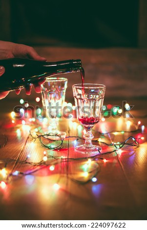 Christmas: pouring red wine on table with colorful lights - stock photo