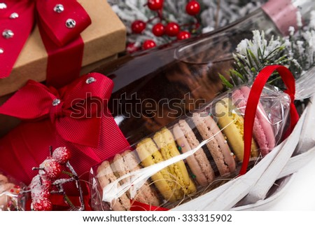 christmas present in basket with sweet pastry, bottle of wine and decor - stock photo